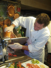 Chef slicing prosciutto